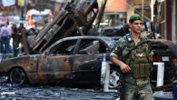 A Lebanese army soldier passes in front of burned cars at the site of a car bomb explosion in southern Beirut, on August 16, 2013 (photo credit: AP Photo/Hussein Malla, File)