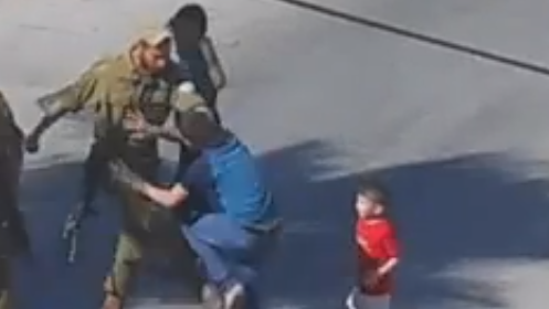 A soldier seen kicking a Palestinian boy in Hebron (photo credit: YouTube screen cap)