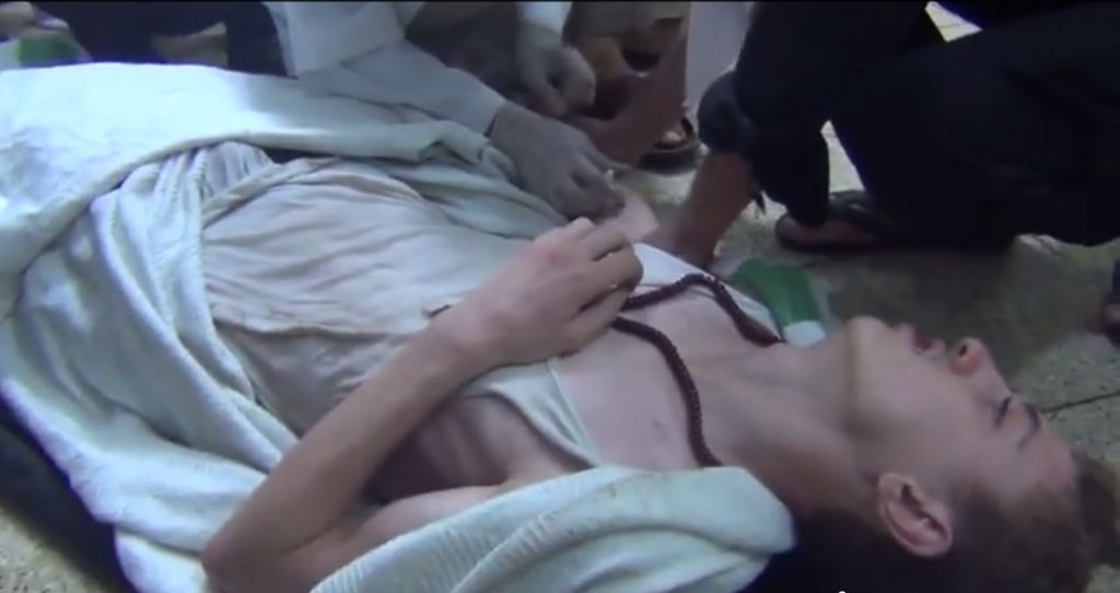 A man suffers a seizure in this video porportedly showing victims of a chemical attack outside Damascus Wednesday. (Screenshot: YouTube)