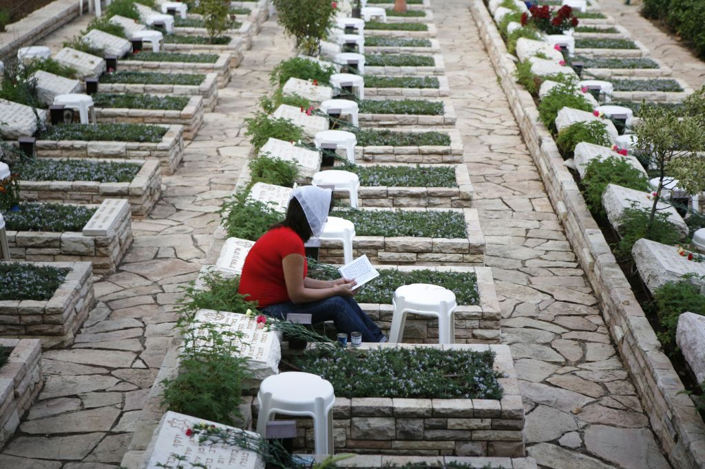 A  woman sits next to the grave of fallen soldier from the 1973 Yom Kippur War, in the Mount Herzl military cemetery in Jerusalem (Photo credit: Michal Fattal/Flash90)