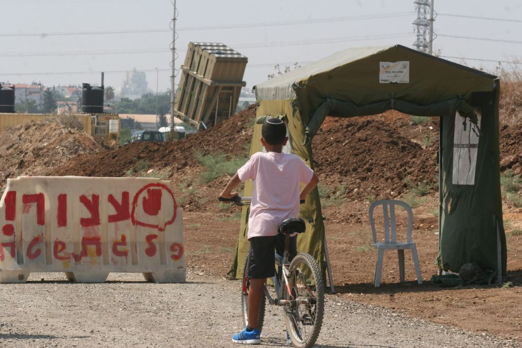 A boy next to a stop sign in front of an Iron Dome anti-missile battery near Tel Aviv. (photo credit: Roni Schutzer/Flash90)