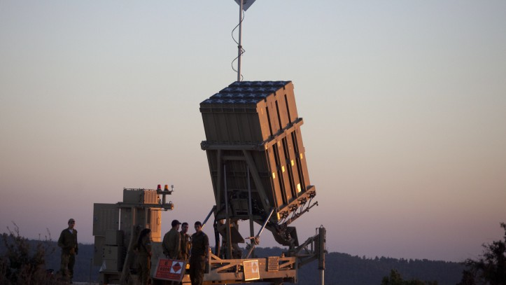 Israeli soldiers walk by an Iron Dome missile defense system deployed near Jerusalem (photo credit Flash90)