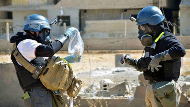 Members of a UN investigation team take samples from sand near a part of a missile  in Syria, In this Aug. 28, 2013. (photo credit: AP/United Media Office of Arbeen