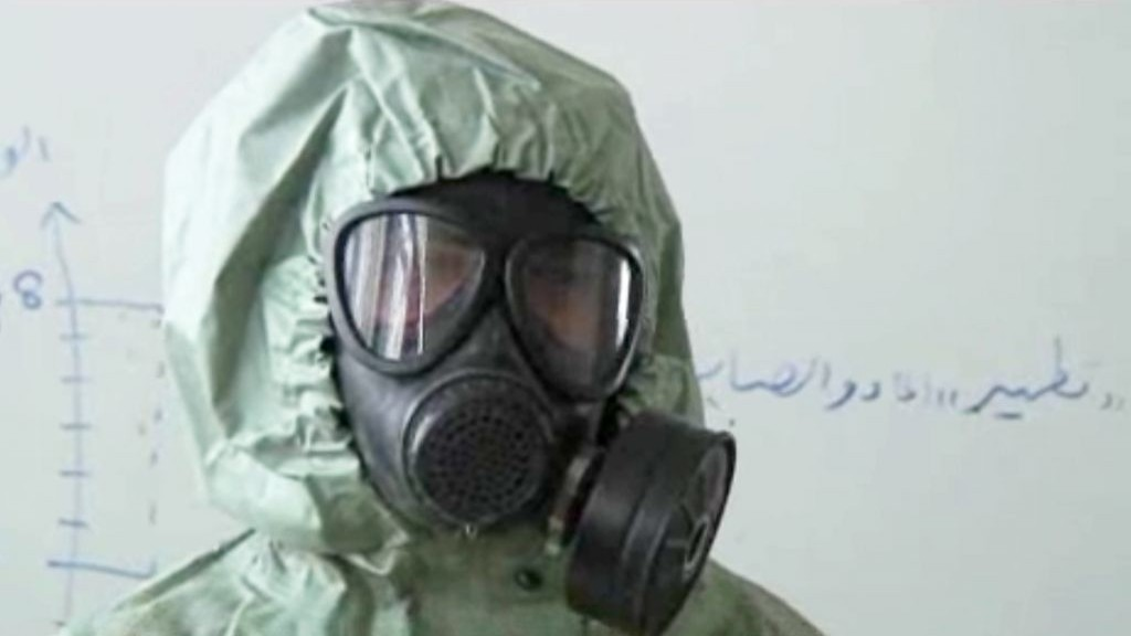 This image made from a video posted on September 18, 2013, shows a student wearing a gas mask and protective suit during a classroom session on how to respond to a chemical weapons attack in Aleppo, Syria (photo credit: AP)