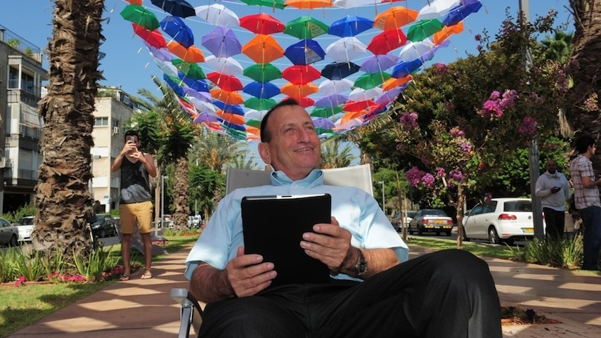 Tel Aviv Mayor Ron Huldai surfs the Internet under a roof of 600 colorful umbrellas decorating Rothschild Boulevard, announcing the new 'wifi cloud' in the city (Photo credit: Kfir Sivan)