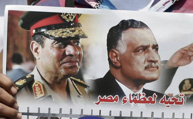 In this July 12, 2013, photo, Egyptian policemen hold a picture with portraits of Army Chief Gen. Abdel Fattah el-Sissi and former Egyptian president Gamal Abdel Nasser at Tahrir Square, in Cairo. Arabic in the picture reads,'Salutation to the great men of Egypt,' (photo credit: AP)