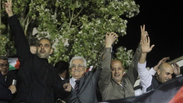 Palestinian Authority President Mahmoud Abbas, flanked by newly released Palestinian prisoners, greets the crowd in Ramallah, early Wednesday, October 30, 2013 (photo credit: Issam Rimawi/Flash90)