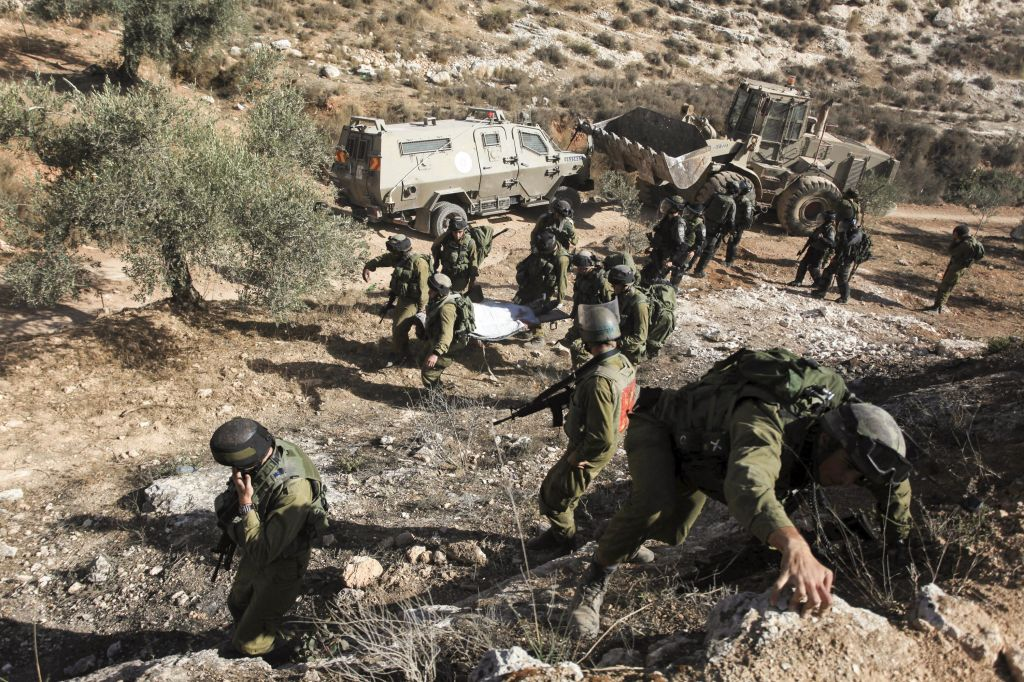 IDF soldiers carry away the body of armed Palestinian terror suspect Mohamed Aazi near the West Bank village of Bil'in, near Ramallah October 22, 2013. Aazi, 28, was wanted for his alleged involvement in the November 21, 2012 Tel Aviv bus bombing (Photo credit: Issam Rimawi /FLASH90)