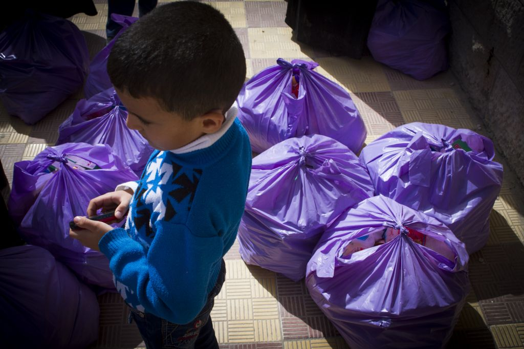 A Syrian boy stands amid the distribution bags, paid for by Jewish donors. (photo credit: Mickey Alon)