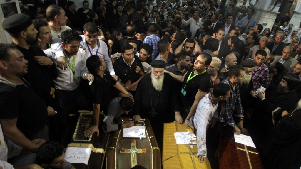 Egyptian mourners gather in front of the coffins of four Coptic Christians who were killed late Sunday, during their funeral in Warraq's Virgin Mary church in Cairo, Egypt, on Monday (photo credit: AP/Khalil Hamra)