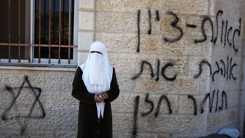 A Palestinian woman stands next to a vandalized mosque in the West Bank village of Burka, near Ramallah, Thursday, Oct. 10, 2013 (photo credit: AP/Majdi Mohammed)