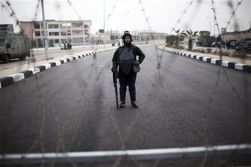 A riot policeman stands guard behind barbed wire outside of a police academy compound were the trial of ousted President Mohammed Morsi will be held in Cairo, Egypt, Monday, Nov. 4, 2013. The deposed Islamist president is to go on trial Monday on charges of incitement of violence and murder, in what will be Morsi's first public appearance since his ouster in a coup on July 3. (photo credit: AP Photo/Manu Brabo)