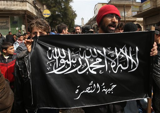 Anti-Syrian President Bashar Assad protesters hold the Jabhat al-Nusra flag, as they shout slogans during a demonstration, at Kafranbel town, in Idlib province, northern Syria March 1, 2013. Leader of al-Qaeda in Syria Abu Mohammad al-Golani heads the al-Nusra Front rebel faction. (photo credit: (AP Photo/Hussein Malla, File)
