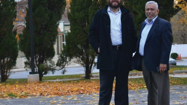 Rabbi Yossi Kaplan and Mohammad Aziz in the parking lot that Chabad and the Islamic Center share. Photo via Chabad.org