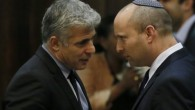 Finance Minister Yair Lapid (L) seen speaking with Minister of Economics and Trade  Naftali Bennett during a plenum session in the assembly hall