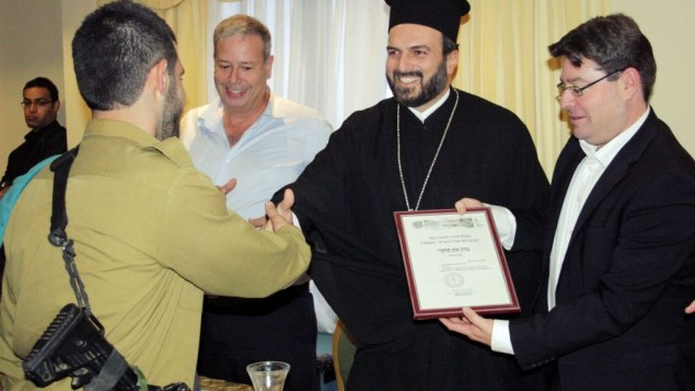 A Christian Arab soldier receiving a certificate of appreciation from Father Gabriel Naddaf during a recent event in Nazareth (photo credit: courtesy IDF Spokesperson's Unit)