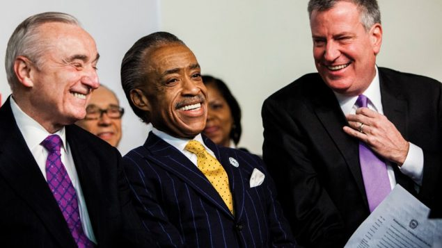 Rev. Al Sharpton enjoys a light moment with Police Commissioner William Bratton, left, and Mayor Bill de Blasio. Getty Images