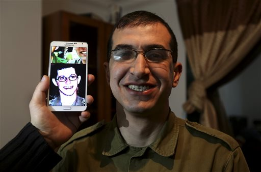 Director Majed Jundiyeh holds a mobile phone to compare the image of Gilad Shalit to the likeness of actor Mahmoud Karira, who will play the character of Shalit in a movie being made in Gaza called 'Losing Shalit,' Jan. 26, 2014 (photo credit: Hatem Moussa/AP)