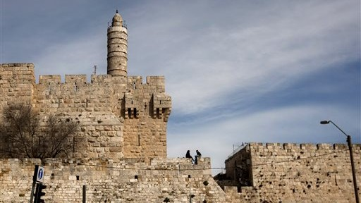 In this March 7, 2012 file photo, a couple sits next to the Tower of David on the wall surrounding Jerusalem's Old City. (AP/Sebastian Scheiner)