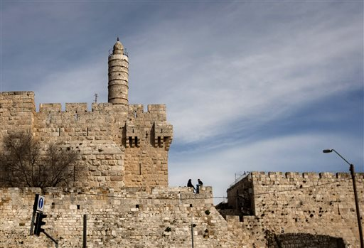 In this March 7, 2012 file photo, a couple sits next to the Tower of David on the wall surrounding Jerusalem's old city. (photo credit: AP/Sebastian Scheiner, File)