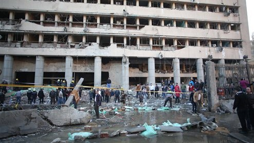 Egyptian police officers and firefighters gather at the Egyptian police headquarters after a blast in downtown Cairo on Friday, January 24, 2014. (photo credit: AP/Khalil Hamra)