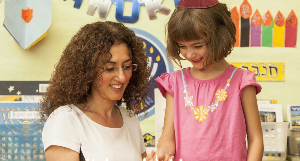Kindergarten teacher Nirit Yakov lighting a menorah with a student at Tehiyah Day School in California. (Illustrative photo: Courtesy of Tehiyah Day School/JTA)