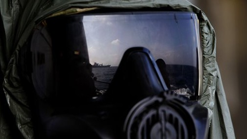 A crew member of the Danish warship Esbern Snare wears a protective mask which shows the reflection of the Danish cargo ship Ark Futura, during emergency drills on the sea between Cyprus and Syria, Sunday, Jan. 5, 2014 (photo credit: AP/Petros Karadjias)