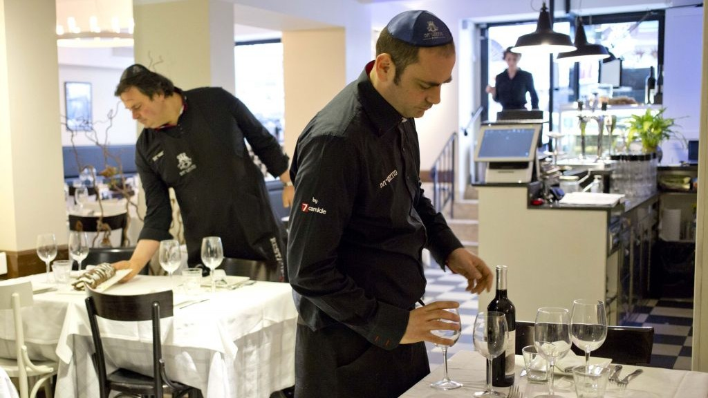 Ba'Ghetto restaurant owners Ilan Dabush, left, and his brother Amit work in their restaurant, which was tapped to cater Pope Francis' luncheon. (photo credit: AP/Alessandra Tarantino)