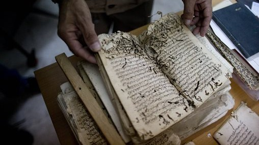 An employee shows an old manuscript at the al-Aqsa mosque compound library in Jerusalem. The library has a collection of some 4,000 old manuscripts with about a quarter considered in poor condition. (photo credit: AP Photo/Dusan Vranic)