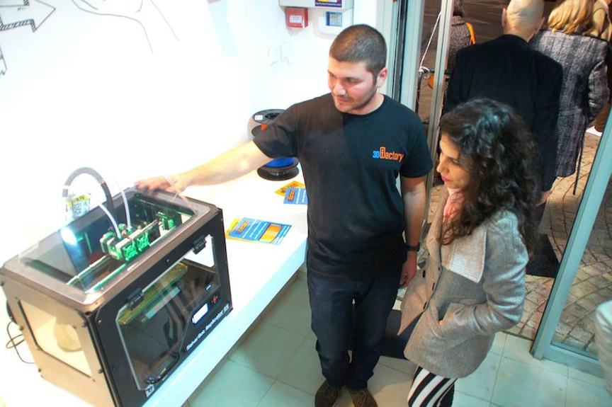 A customer checks out a 3D printer in action ((Photo credit: Courtesy)
