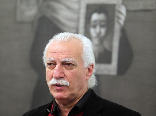 A picture taken on February 6, 2014 shows Syrian artist Youssef Abdelke talking about his paintings displayed at an art gallery in Beirut (Photo credit: Joseph Eid/AFP)