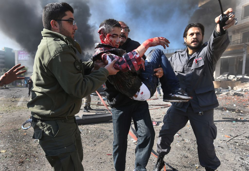 Lebanese men carry a wounded man at the site of an explosion near the Kuwaiti Embassy and Iran's cultural center, in the suburb of Beir Hassan, Beirut, Lebanon, Wednesday, February 19, 2014 (photo credit: AP/Hussein Malla)