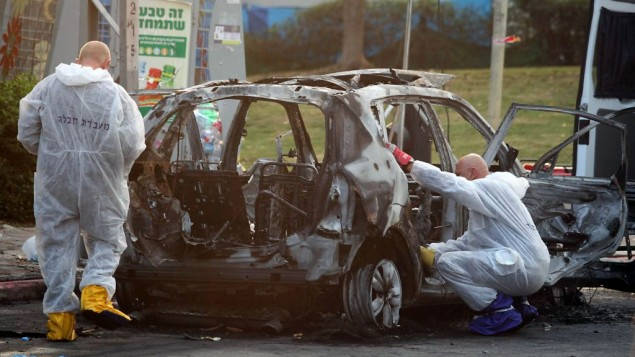 Members of the police bomb squad investigate a car that exploded in the city of Petah Tikvah, February 3, 2014. (Photo credit: Gideon Markowicz/Flash90/File)