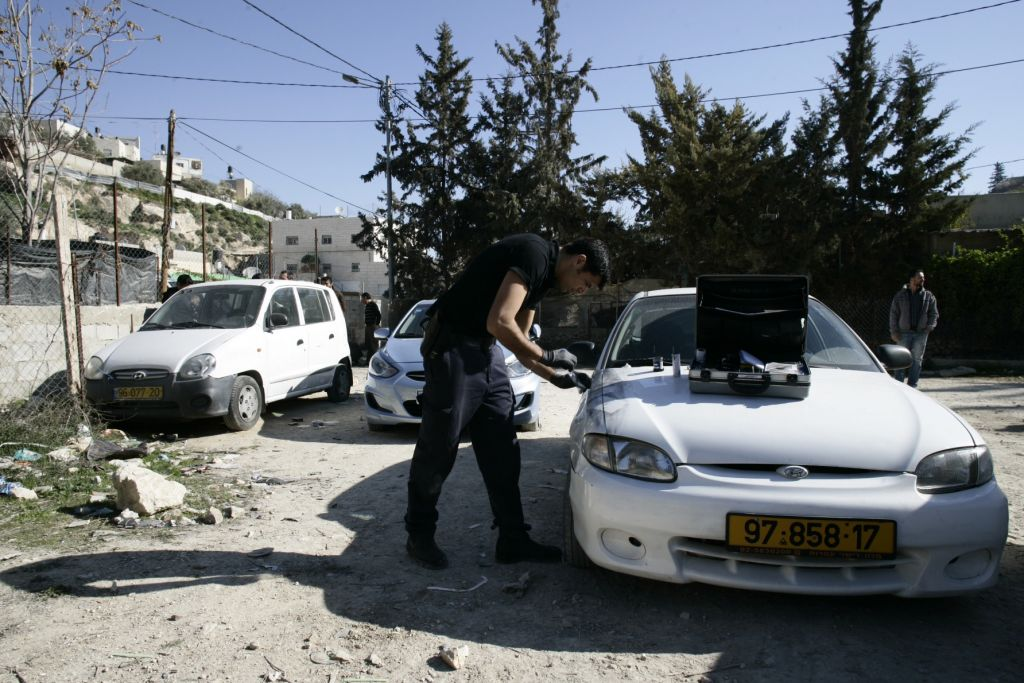 An Israeli police officer inspects a car vandalized in an apparent price tag attack in East Jerusalem, Monday, February 10, 2014 (photo credit: Flash90)