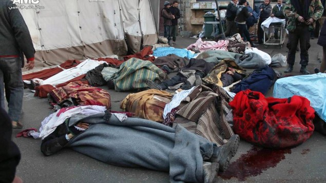 Syrians stand near the bodies of people who were killed in a reported government airstrike, outside a field hospital in Aleppo, Syria, on December 15, 2013 (photo credit: AP/Aleppo Media Center/File)