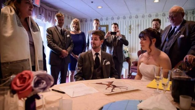 Cheryl Silvers and Eric Doades sign the ketubah at their interfaith wedding. Courtesy of Cheryl Silvers and Eric Doades