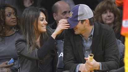 Actress Mila Kunis playfully pulls down the hat of actor Ashton Kutcher before a Los Angeles Lakers' NBA basketball game against the Utah Jazz,  January 3, 2014, in Los Angeles. (AP/Mark J. Terrill)