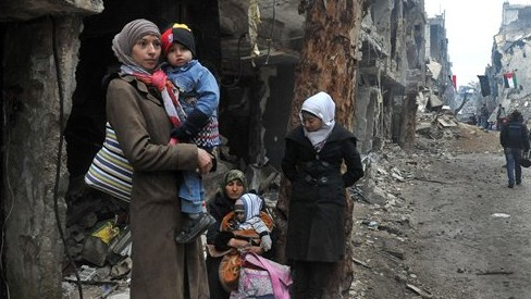 Residents of the besieged Yarmouk Palestinian refugee camp wait to leave the camp, on the southern edge of the Syrian capital Damascus, Syria, Tuesday, Feb. 4, 2014 (photo credit: AP/SANA)