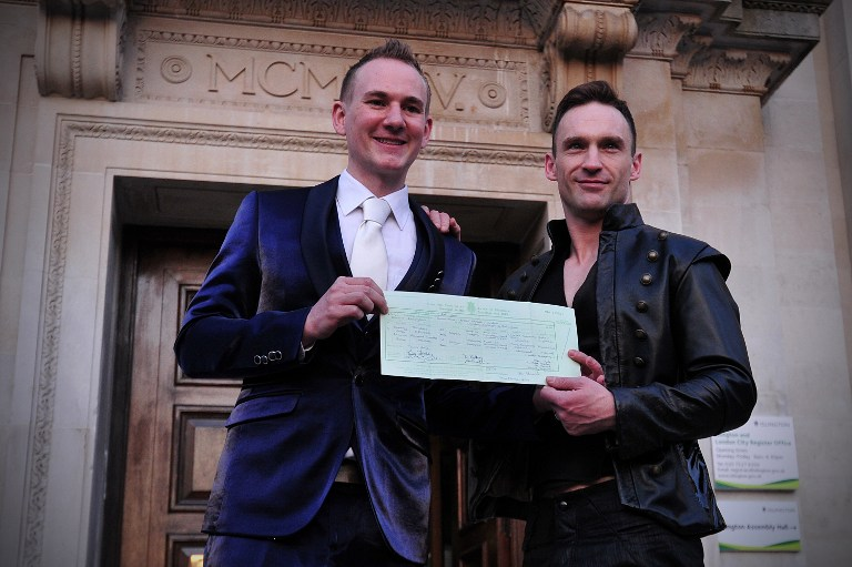 Tim Jarmaine-Groves (L) and his husband, Richard Jarmaine-Groves, hold their wedding certificate as they pose for photographs after their same-sex wedding in north London on March 29, 2014 (photo creit: AFP/Carl Court)