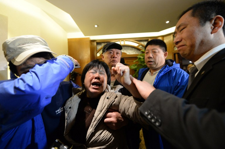 Angry relatives of missing passengers on Malaysia Airlines flight MH370 weep after hearing the news that the plane plunged into Indian Ocean, at a hotel in Beijing on March 24, 2014.  (photo credit: AFP/ GOH CHAI HIN)