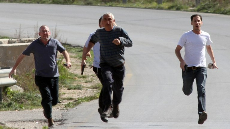 Armed settlers are seen running after a Palestinian journalist's car was attacked near the West Bank settlement of Beit El on Friday (photo credit: AFP)