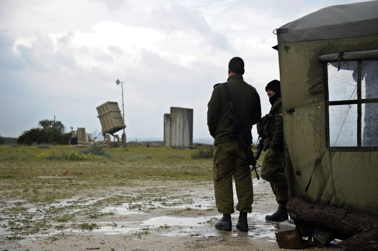 Two Israeli soldiers stand near an Iron Dome battery near the southern Israeli city of Ashkelon on March 13, 2014. (photo credit:AFP/DAVID BUIMOVITCH)