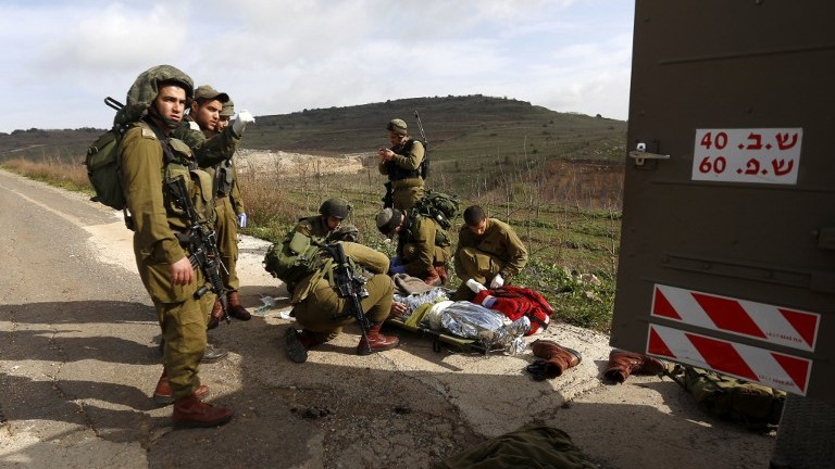 IDF soldiers prepare to evacuate a comrade injured in a blast on the border with Syria near the village of Majdal Shams on Tuesday, March 18, 2014 (photo credit: AFP/Jalaa Marey)