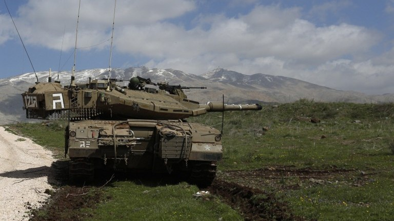 An Israeli army tank is seen stationed near the village of Majdal Shams, on March 19, 2014, in the Golan Heights. (photo credit: AFP/Jalaa Marey)