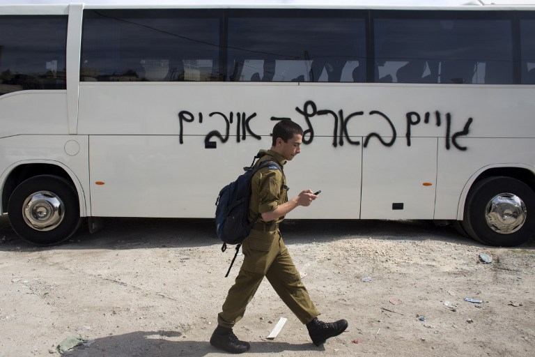 An IDF soldier walks past a bus on which suspected Jewish vandals painted graffiti reading 'Gentiles in the land are enemies' on March 24, 2014 in Beit Hanina (photo credit: AFP/Ahmad Gharabli)