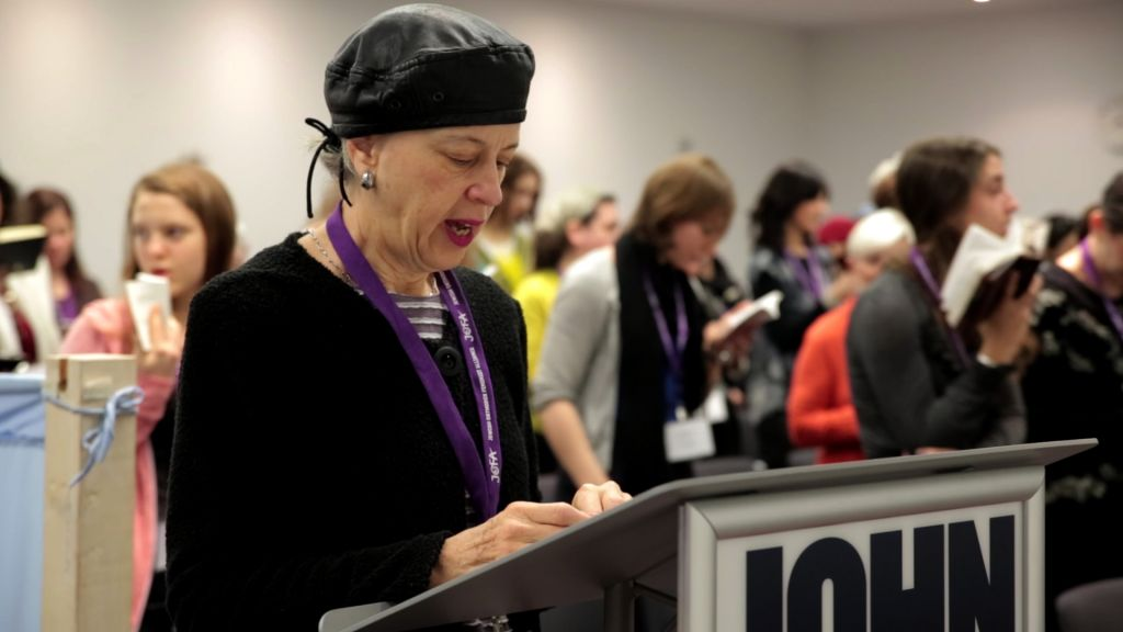 Illustrative: A woman leads a partnership minyan at a conference in New York of the Jewish Orthodox Feminist Alliance (JOFA), December 2013. (Mike Kelly/JTA)
