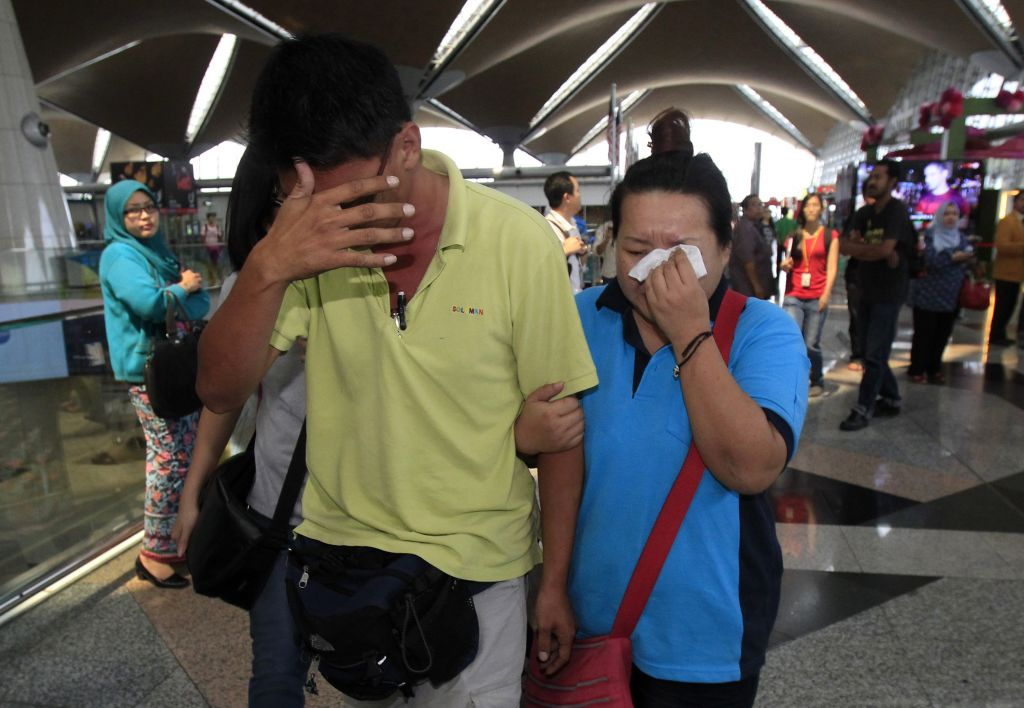 A woman wipes her tears after walking out of the reception center and holding area for family and friends of passengers aboard a missing Malaysia Airlines plane, at Kuala Lumpur International Airport in Sepang, Saturday, March 8, 2014. (photo credit: AP Photo/Lai Seng Sin)