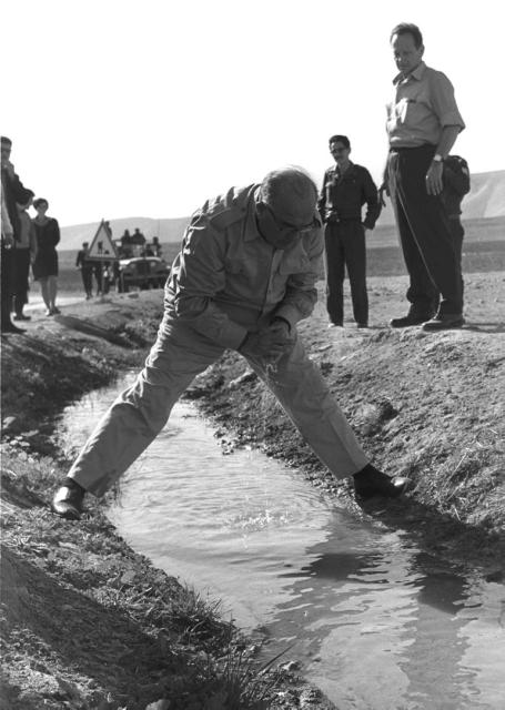 Levi Eshkol straddles the Jordan River (photo credit: GPO)