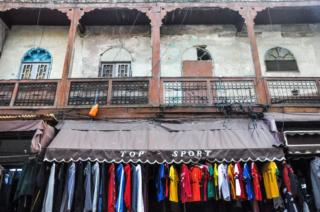 Old mixes with new in the mellah of Fez: Former Jewish homes, with outward-facing balconies, with t-shirt shops below them. (photo credit: Michal Shmulovich)