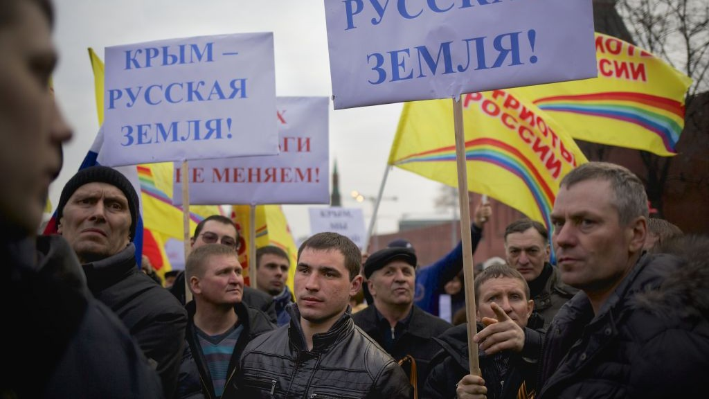 """Pro-Putin demonstrators hold posters reading """"Crimea is Russian land!"""" as they gather on Red Square in Moscow, Russia, Friday, March 7, 2014. (photo credit: AP/Alexander Zemlianichenko)"""